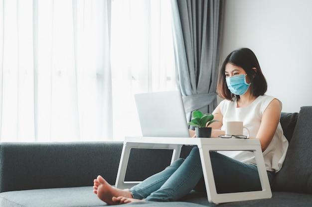 Azjatycka kobieta jest ubranym twarzy maskę pracuje w domu