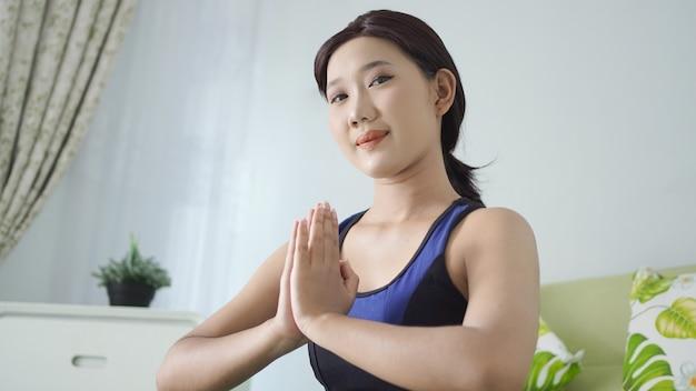 Azjatycka kobieta joga w domu robi ćwiczenia dłoni z naciskiem