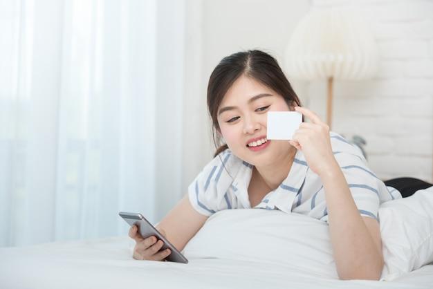 Azjatycka kobieta kłaść na łóżku trzyma mądrze telefon