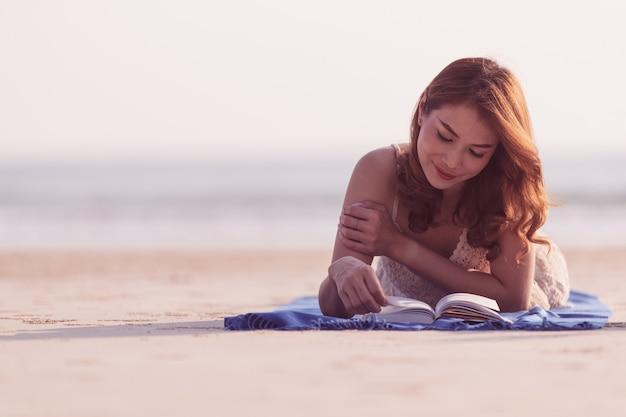Azjatycka kobieta kłaść w dół na plaży i czytaniu