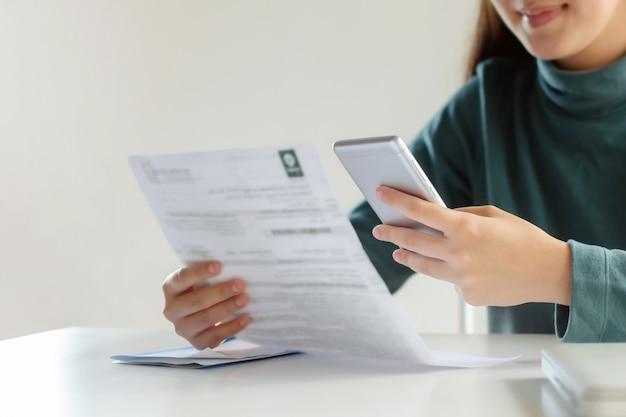 Azjatycka kobieta klienta korzystająca z inteligentnego telefonu komórkowego do skanowania i płatności online z rachunkiem kosztów budżetu rodzinnego na biurku w biurze domowym, planuj oszczędności kosztów, inwestycje, finanse biznesowe, koncepcja wydatków