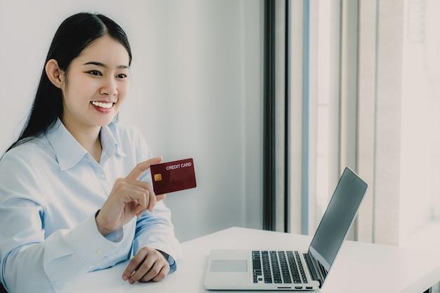 Azjatycka kobieta konsumencka posiadająca kartę kredytową gotowa do wydawania pieniędzy na zakupy online zgodnie z produktem