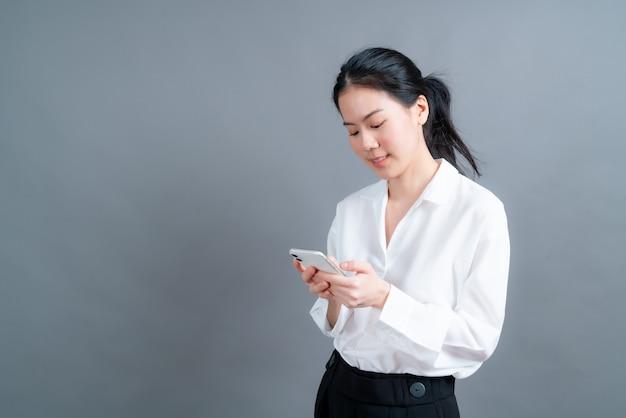 Azjatycka kobieta korzystająca z aplikacji na telefony komórkowe, ciesząca się komunikacją na odległość online w sieci społecznościowej lub robieniem zakupów na białym tle