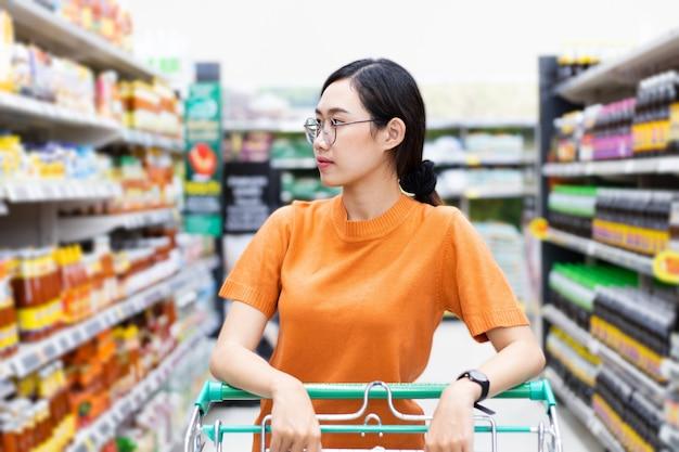 Azjatycka kobieta korzystająca z zakupów w centrum handlowym obsługuje wózek na zakupy patrząc na półkę w supermarkecie
