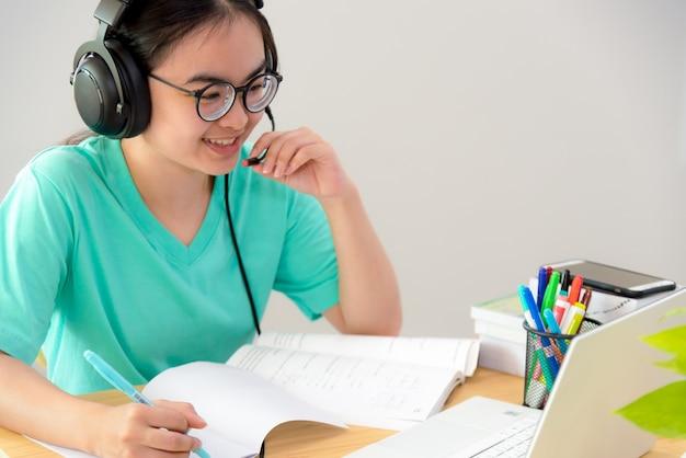 Azjatycka kobieta, która chce rozmawiać podczas wideokonferencji na laptopie, uczennice mówią, odpowiadają za pomocą zestawu słuchawkowego, mikrofon, klasa, uniwersytet, nauka, internet, edukacja na odległość, z domu