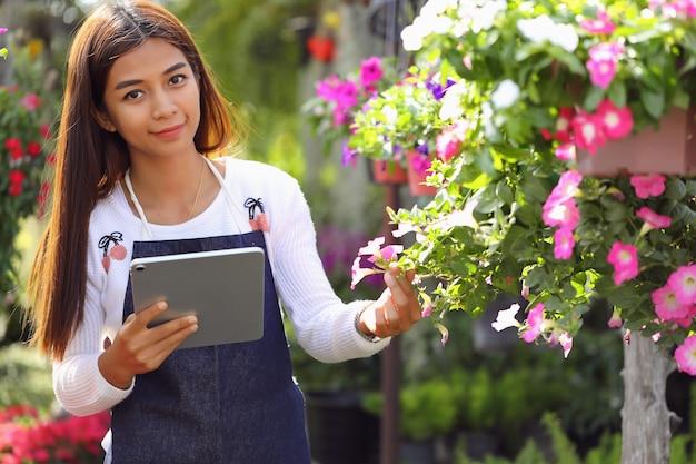 Azjatycka kobieta, która jest właścicielem firmy zajmującej się ogrodem kwiatowym, liczy kwiaty zgodnie z zamówieniem klienta.