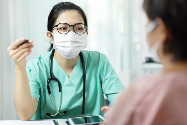 Azjatycka kobieta lekarka w zieleni mundurze jest ubranym szkła i chirurgiczną maskę opowiada, konsultuje i daje rada starszej kobiety pacjentowi w pokoju medycznym przy szpitalem.
