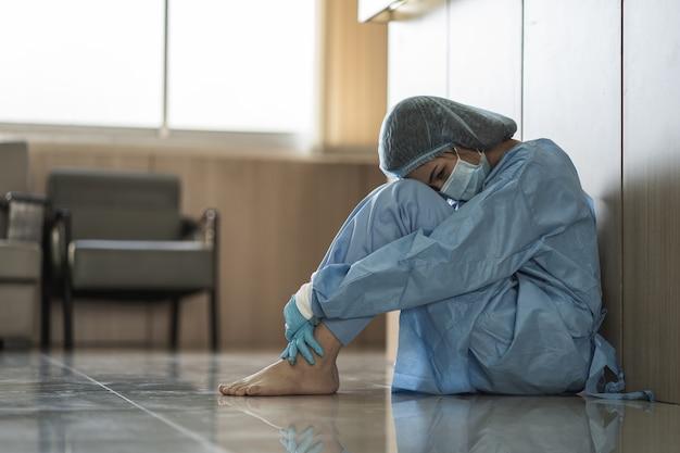 Azjatycka kobieta lekarz nosi chirurgiczną maskę na twarz, siedząc na podłodze, zmęczona pracą, ponieważ wpływ wybuchu pandemii covid-19, smutek pracownik opieki zdrowotnej kobieta, koncepcja medyczna i zdrowotna