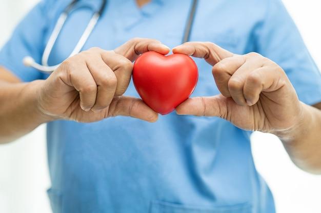 Azjatycka kobieta lekarz trzymająca czerwone serce na oddziale szpitala pielęgniarskiego, zdrowa, silna koncepcja medyczna