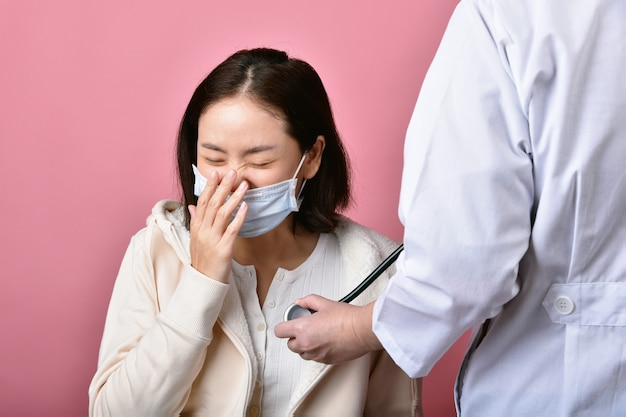 Azjatycka kobieta ma alergię na ból gardła i kaszel w masce, kichanie i kaszel rozprzestrzeniają kroplę choroby koronawirusa, lekarz przesiewowy zakażony pacjentem zakażonym covid-19 w szpitalu.