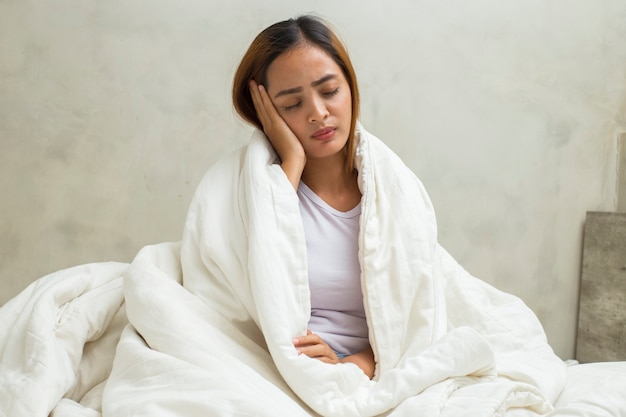 Azjatycka kobieta ma problemy z gorączką i kaszlem śpiąc w łóżku w domu