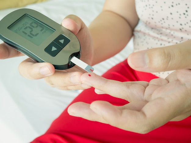 Azjatycka kobieta mierzy poziom glukozy za pomocą cyfrowego glukometru, test cukrzycy