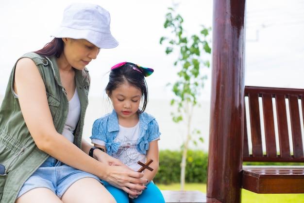 Azjatycka kobieta modli się z małą dziewczynką na świeżym powietrzu.