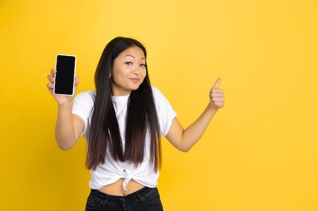Azjatycka kobieta na żółtej ścianie, emocje