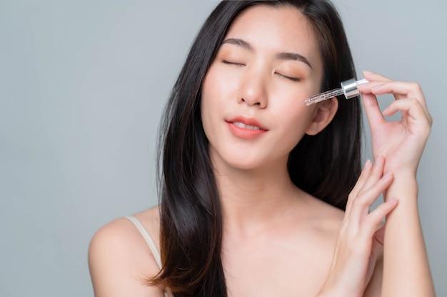 Azjatycka kobieta nakładająca na twarz serum hialuronowe za pomocą pipety
