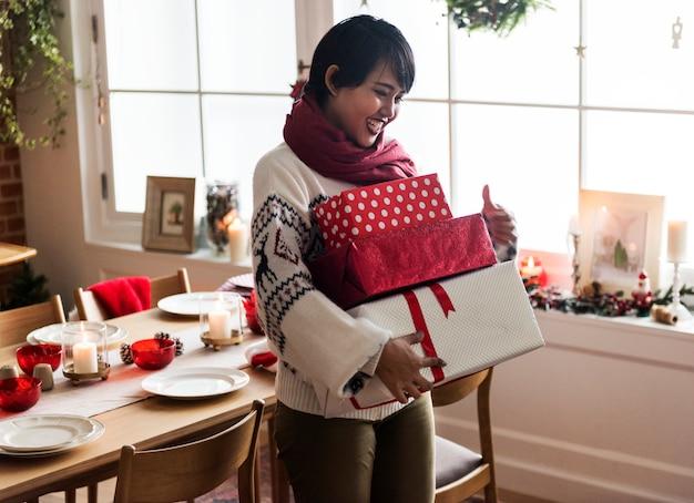 Azjatycka kobieta niesie bożenarodzeniowych prezentów pudełka