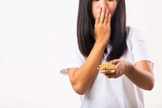 Azjatycka kobieta nieszczęśliwa problem ze słabymi włosami trzyma szczotkę do włosów z uszkodzonymi, długimi włosami wypadającymi w grzebieniu