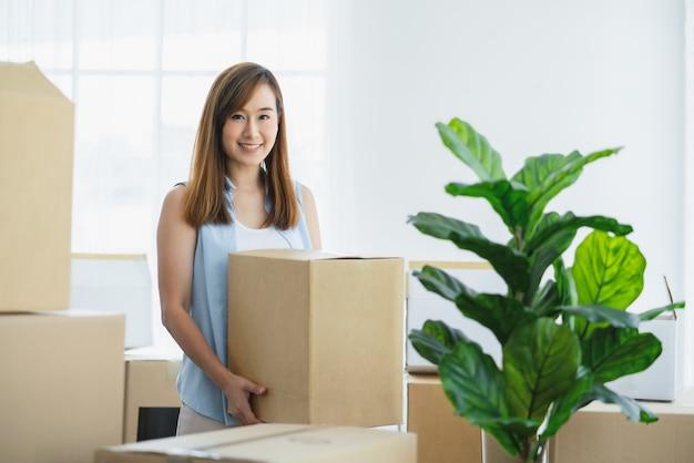 Azjatycka kobieta niosąca kartony przeprowadzająca się do nowego domukoncepcja zakupu nieruchomości lub nieruchomości
