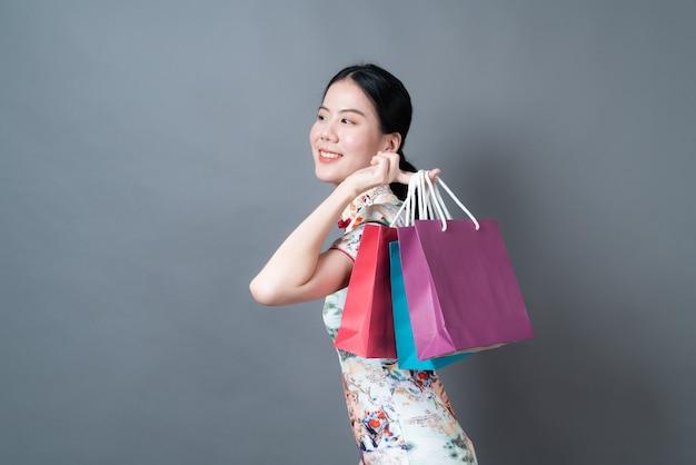 Azjatycka kobieta nosi chiński tradycyjny strój z ręki trzymającej torbę na zakupy na szarej ścianie