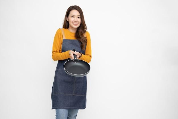 Azjatycka kobieta nosi fartuch kuchenny, gotowanie i trzymanie patelni.