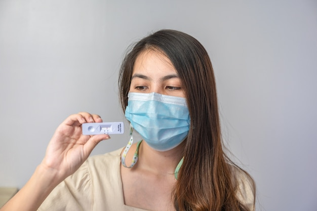 Azjatycka kobieta nosi maskę na twarz, wykazując negatywny wynik szybkiego testu antygenowego do użytku domowego. brak infekcji covid-19, koronawirusa