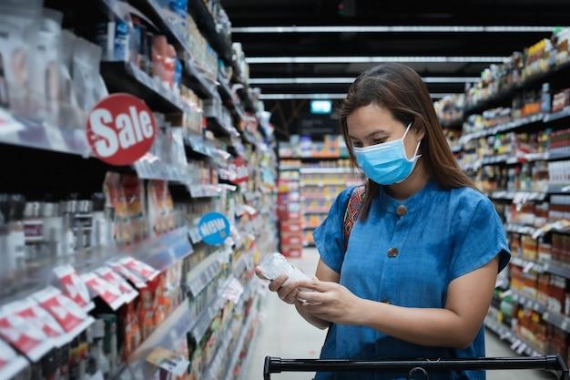 Azjatycka kobieta nosi maskę na twarzy podczas zakupów w supermarkecie dla opieki zdrowotnej