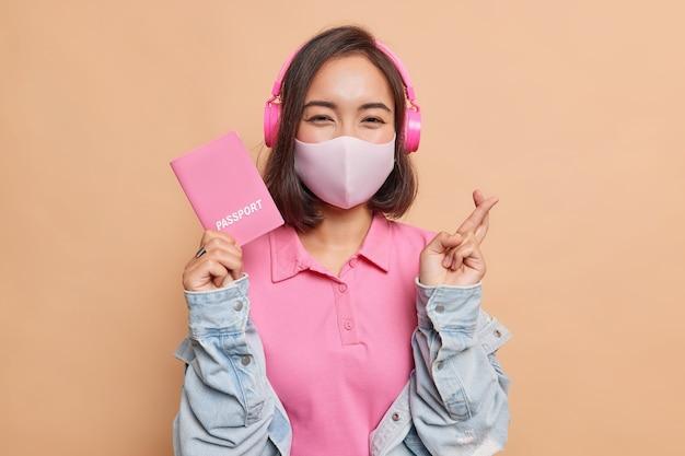 Azjatycka kobieta nosi ochronną jednorazową maskę przeciwko koronawirusowi zamierza podróżować za granicę słucha muzyki przez bezprzewodowe słuchawki trzyma paszport nosi różową koszulkę dżinsową kurtkę odizolowaną na beżowej ścianie