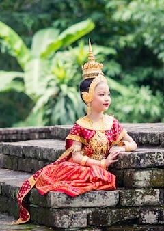 Azjatycka kobieta nosi typową, tradycyjną tajską sukienkę, to dosłownie oznacza