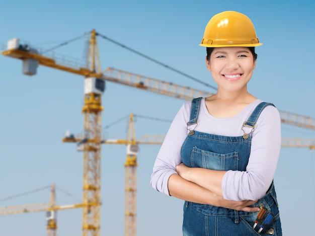 Azjatycka kobieta nosi żółty kask ochronny z tłem budowy