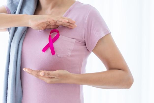 Azjatycka kobieta nosząca chustę na głowę z różową wstążką ręcznie sprawdzająca guzki na piersi pod kątem oznak raka piersi piersi wyizolowanego w oknie w sypialni w domu, opieka zdrowotna, medycyna