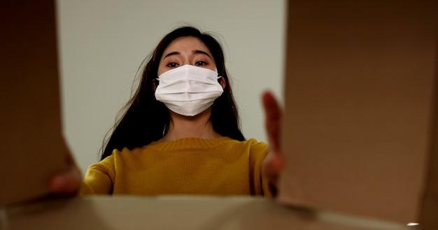 Azjatycka kobieta nosząca maskę ochronną przygotowuje i pakuje paczkę do dostarczenia do klienta