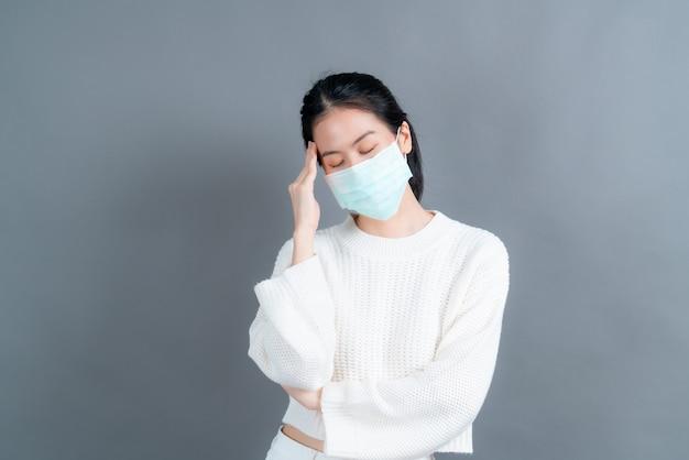 Azjatycka kobieta nosząca medyczną maskę na twarz chroni pył z filtra pm2,5, przeciw zanieczyszczeniom, antysmogowi i covid-19 i ma ból głowy na szarej ścianie
