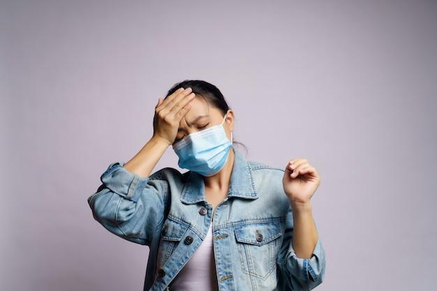 Azjatycka kobieta nosząca ochronną maskę na twarz była chora na ból głowy na białym tle.