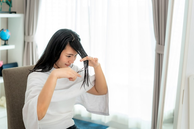 Azjatycka kobieta obcinająca włosy za pomocą nożyczek do strzyżenia w domu, zostaje w domu i schronia się w miejscu podczas izolacji domowej przed nowym koronawirusem lub covid-19