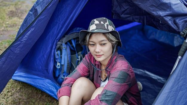 Azjatycka kobieta obozująca w zbiorniku i usiąść w namiocie