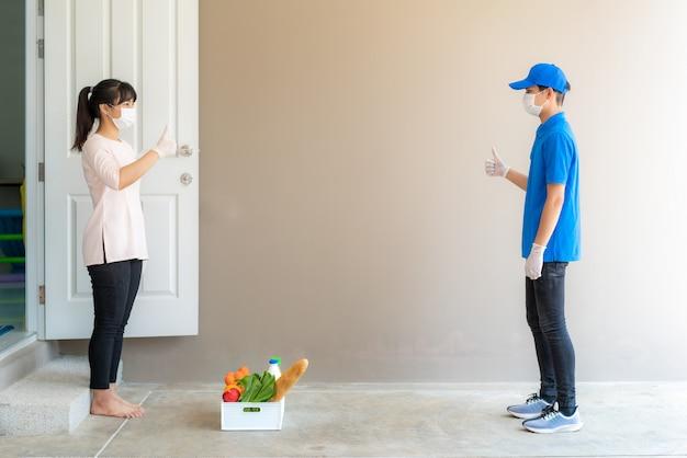 Azjatycka kobieta odbiera pudełko z jedzeniem, owocami, warzywami i napojami oraz kciukiem z formy zbliżeniowej lub bez kontaktu z dostawcą przed domem, aby zdystansować się od ryzyka infekcji.