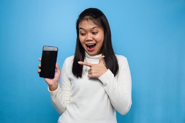 Azjatycka kobieta odizolowana na niebiesko pokazując pusty ekran telefon komórkowy dobre aplikacje polecane aplikacje