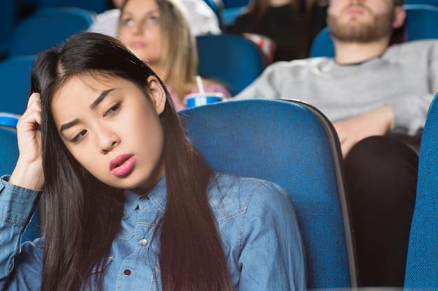 Azjatycka kobieta odwracając znudzony siedzi w kinie