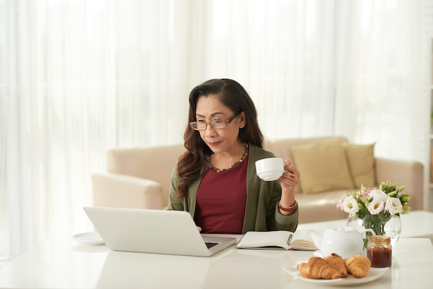 Azjatycka kobieta ogląda coś na laptopie w ranku
