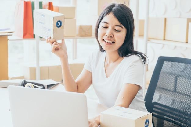 Azjatycka kobieta ono cieszy się podczas gdy używać internet na laptopie i telefonie w biurze