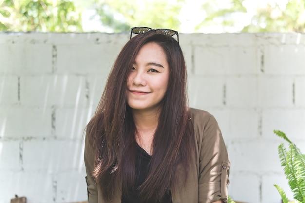 Azjatycka kobieta ono uśmiecha się i siedzi w plenerowym parku z białym cegły ściany tłem
