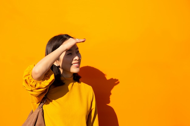 Azjatycka kobieta ono uśmiecha się w pomarańcze wierzchołku z ręką na czole patrzeje kamerę
