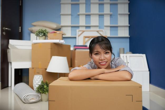 Azjatycka kobieta opiera głowę na łokciach i pakuje pudełko zmęczone rozpakowywaniem w nowym mieszkaniu