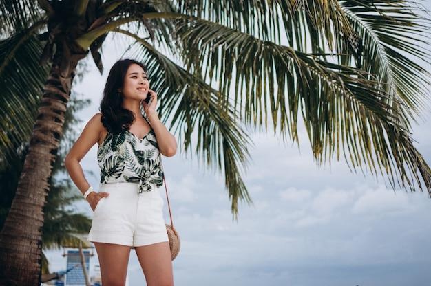 Azjatycka kobieta opowiada na telefonie przy plażą