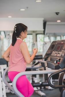 Azjatycka kobieta opracowywał ćwiczenie przy gym odchudzaniem