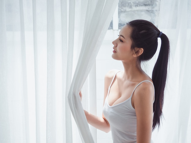 Azjatycka kobieta otwiera nadokienną zasłonę