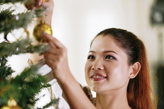 Azjatycka kobieta ozdabia choinkę.