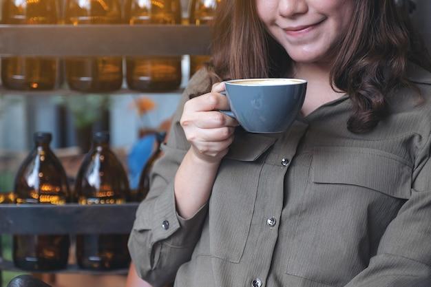 Azjatycka kobieta pachnie i pije gorącą kawę z dobrym samopoczuciem w kawiarni