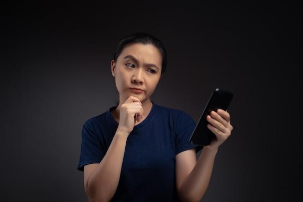 Azjatycka kobieta patrząc na smartfona, czytając wiadomości i czuje się zdezorientowana.