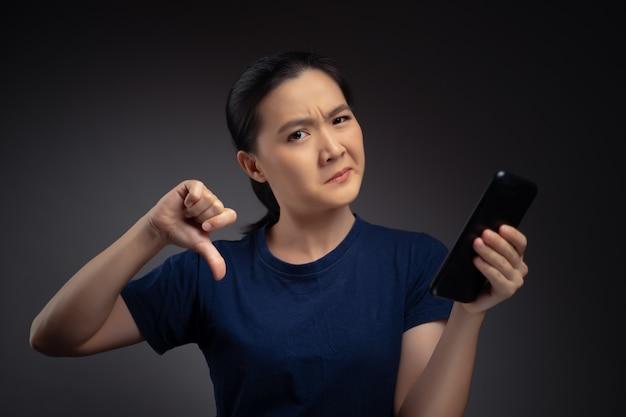 Azjatycka kobieta patrząc na smartfona, czytanie wiadomości i pokazując kciuk w dół.